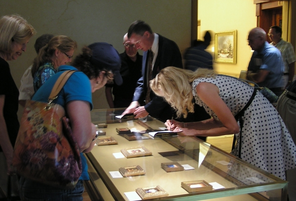 Wes and Rachelle Siegrist signing copies of their book, Exquisite Miniatures, at the R.W. Norton Art Gallery